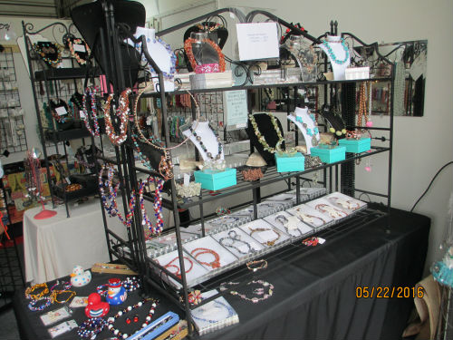 view of six foot table with bakers racks with $20 necklace - Bead and Jewelry Store at Traders Village - San Antonio