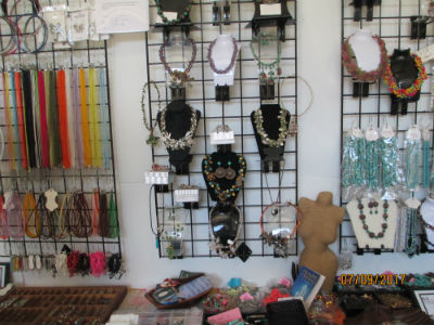 handmade necklaces and silk cords and ribbon cords displayed on back wall of the store
